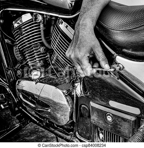 man repairing a classic motorcycle in hdr in black and white - csp84008234
