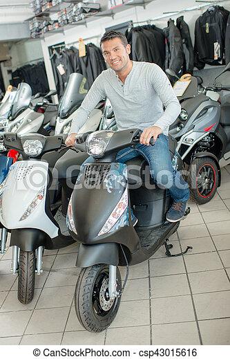Man sat on modern scooter in shop - csp43015616