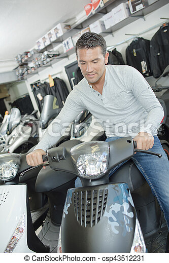 Man sat on modern scooter in showroom - csp43512231