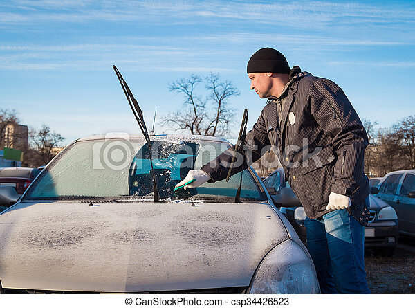 Man scraping front windshield  - csp34426523