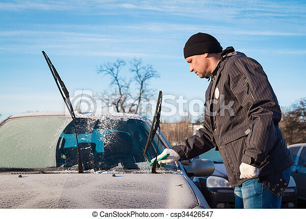 Man scraping front windshield  - csp34426547
