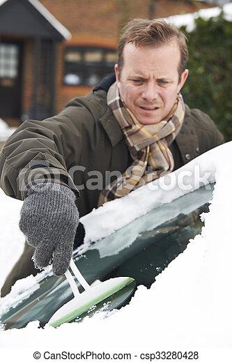 Man Scraping Snow From Car Windscreen - csp33280428