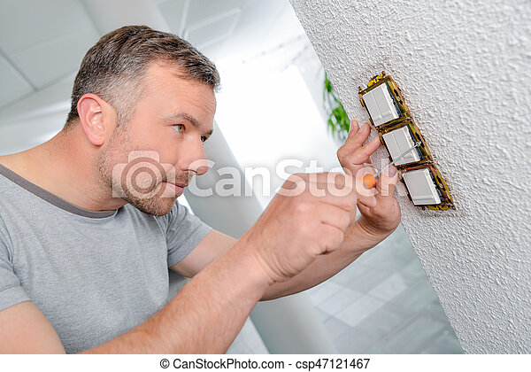 Man screwing row of three switches to wall - csp47121467