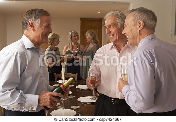 Man Serving Champagne To His Guests At A Dinner Party - csp7424667