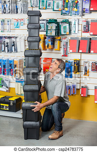 Man Shouting While Carrying Stacked Toolboxes In Store - csp24783775