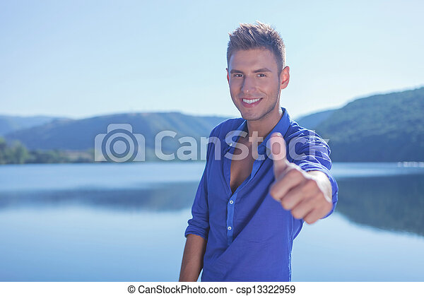 man shows ok by the lake - csp13322959