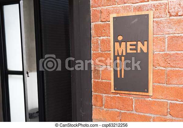 Man signs on public restroom on brick wall - csp63212256