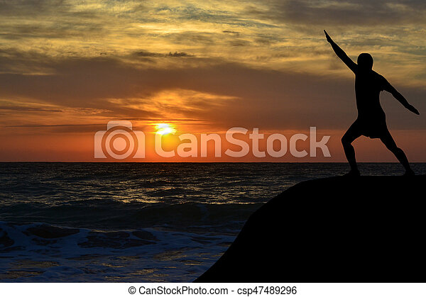 Man Silhouette In A Yoga Pose On The Shore At Sunrise