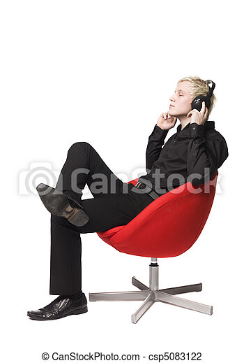 Man siting in armchair listens to music - csp5083122