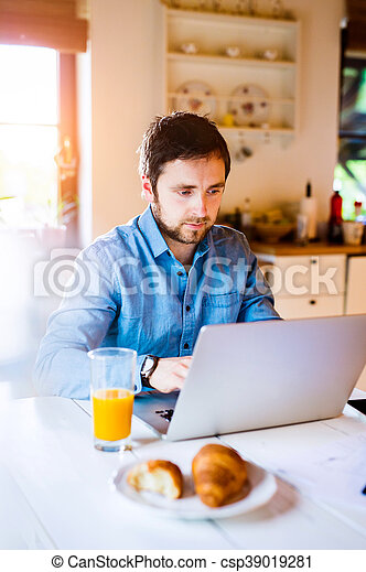 Man sitting at desk working from home on laptop - csp39019281