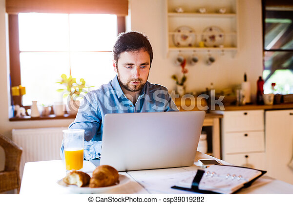 Man sitting at desk working from home on laptop - csp39019282