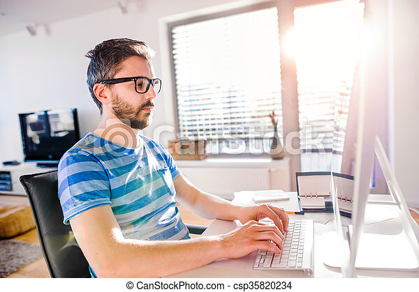 Man sitting at desk working from home on computer - csp35820234