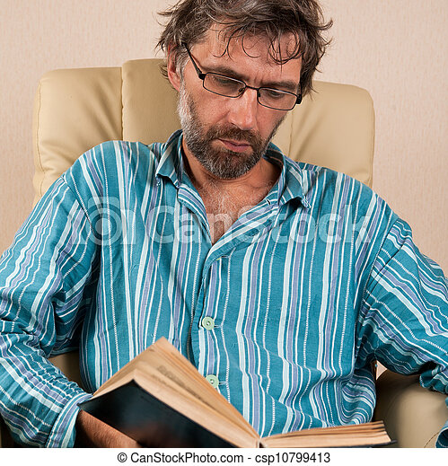 man sitting in chair reading book - csp10799413