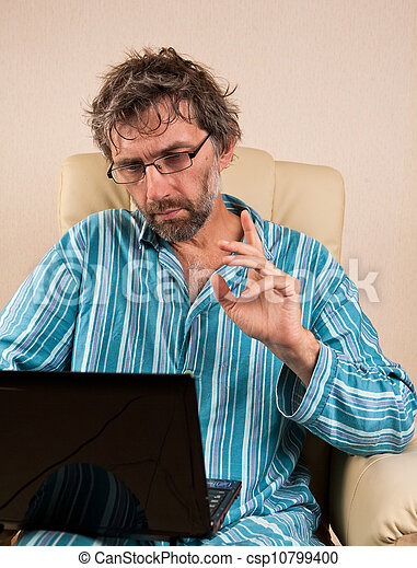 man sitting in chair with laptop - csp10799400