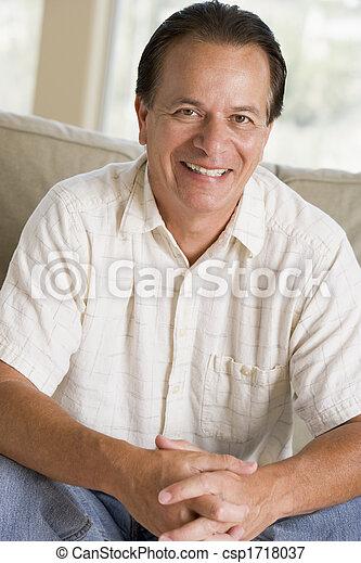 Man sitting in living room smiling - csp1718037
