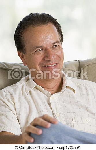 Man sitting in living room smiling - csp1725791