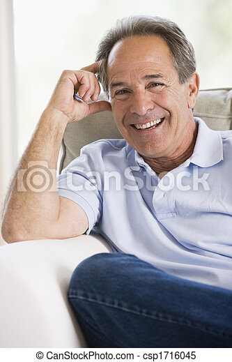 Man sitting in living room smiling - csp1716045