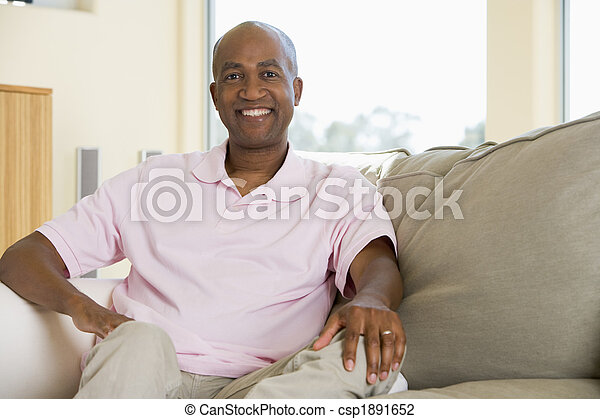 Man sitting in living room smiling - csp1891652