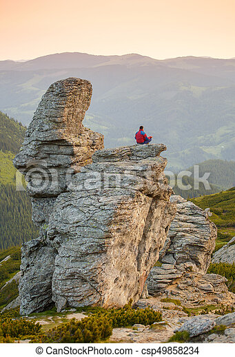 Man Sitting in the Lotus Position on the Rock - csp49858234