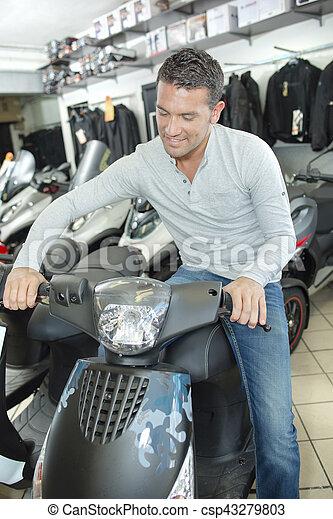 Man sitting on modern scooter - csp43279803