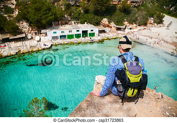 man sitting on the edge of a cliff - csp31723863