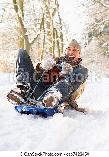 Man Sledging Through Snowy Woodland - csp7423450