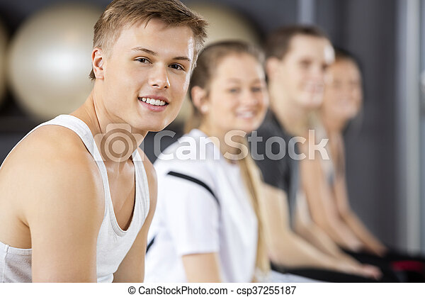 Man Smiling While Sitting With Friends In Gym - csp37255187