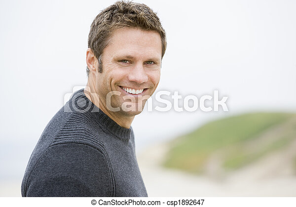 Man standing at beach smiling - csp1892647