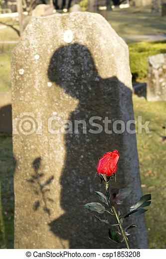 Shadow of a man standing by the grave mourning.