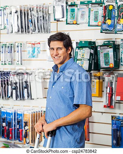 Man Standing In Hardware Store - csp24783842
