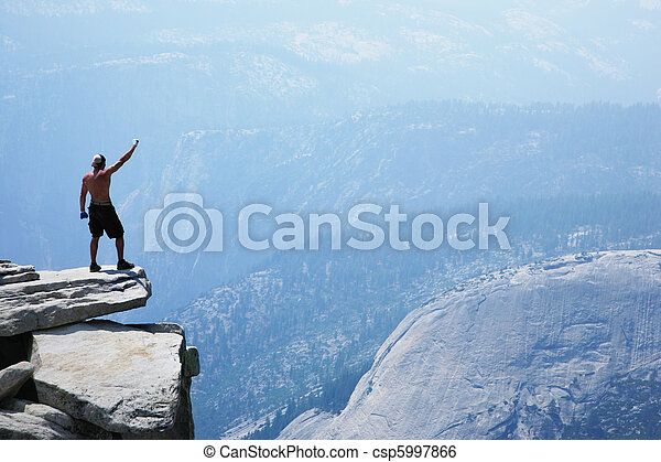 Man standing on top of a cliff with arm raised - csp5997866