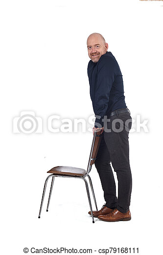 man standing with a chair in white background, side view - csp79168111