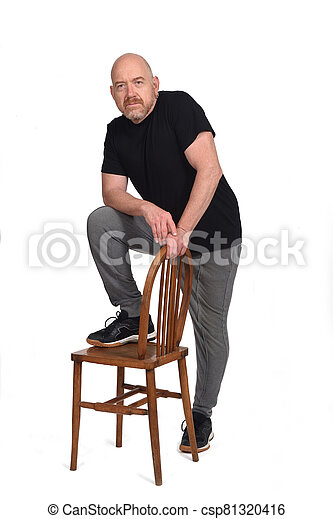 man standing with a chair in white background - csp81320416