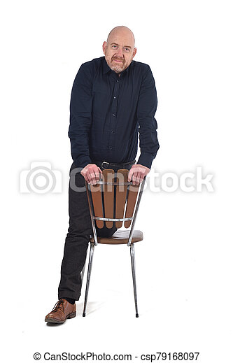man standing with a chair in white background, knees over the chair - csp79168097