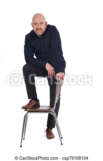 man standing with a chair in white background, foot over the chair - csp79168104
