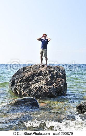 Man stranded on a rock in ocean - csp1290879