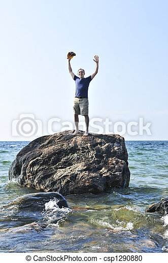 Man stranded on a rock in ocean - csp1290880