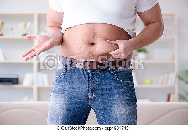 Man suffering from extra weight in diet concept - csp49017451