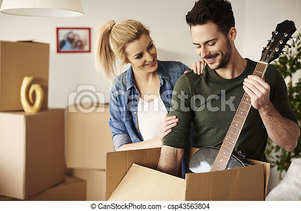Man taking out guitar from the box - csp43563804