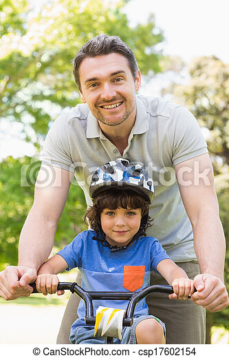 Man teaching his son to ride a bicycle - csp17602154