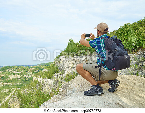 Man tourist is using a smartphone while sitting on the edge of a cliff in the mountains. - csp39769773