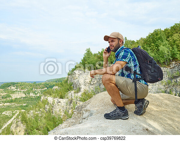 Man tourist is using a smartphone while sitting on the edge of a cliff in the mountains. - csp39769822