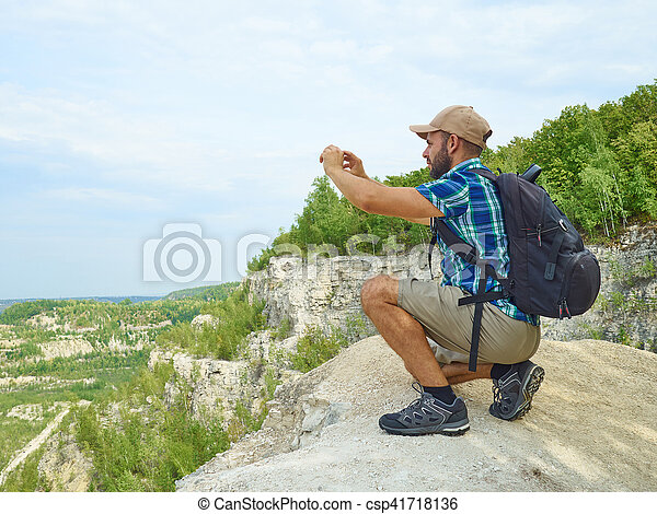 Man tourist is using a smartphone while sitting on the edge of a cliff in the mountains. - csp41718136
