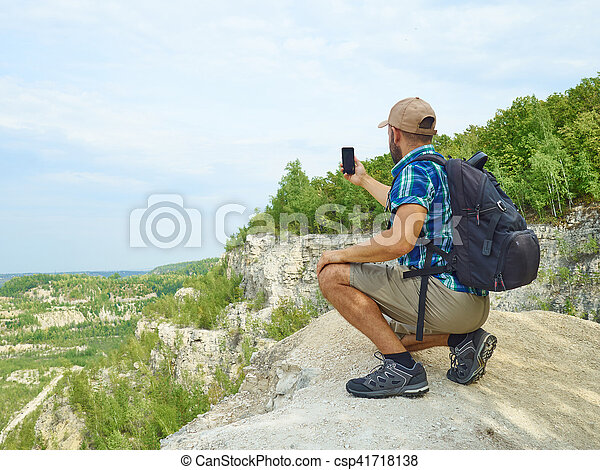 Man tourist is using a smartphone while sitting on the edge of a cliff in the mountains. - csp41718138