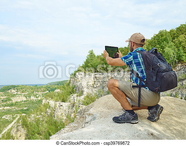 Man tourist uses tablet computer sitting on the edge of a cliff in the mountains. - csp39769872