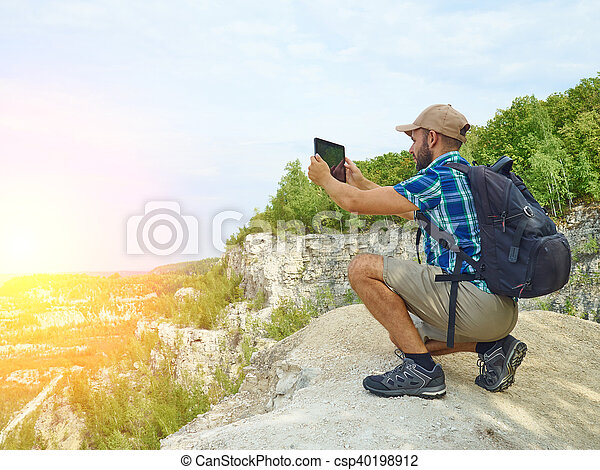 Man tourist uses tablet computer sitting on the edge of a cliff in the mountains. - csp40198912