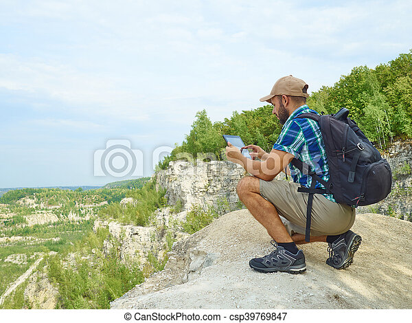 Man tourist uses tablet computer sitting on the edge of a cliff in the mountains. - csp39769847