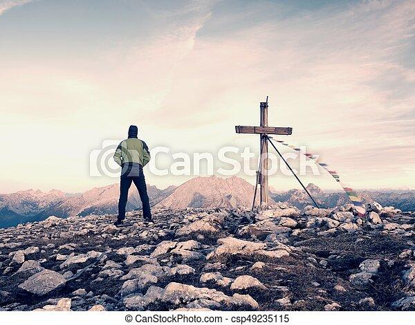 Man tourist walk to cross on the mountain peak. Evening dark, colorful sky during sunset - csp49235115