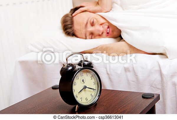 Man trying to sleep, when alarm clock ringing - csp36613041
