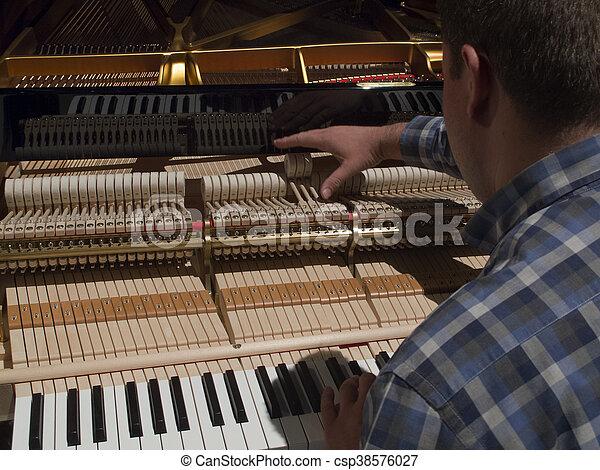 man tunes a piano - csp38576027